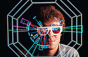 Matthew Jones, wearing 3-D glasses to view computer simulations, from the Stanford Linear Collider (SLC) experiment, seen with a computer-simulated collision event between an electron and a positron. The SLC produces Z-zero particles by this collision process, which takes place at extremely high energies. The Z-zero is one of the mediators of the weak nuclear force, the force behind radioactive decay, and was discovered at CERN in 1983. The scientist is seen wearing special glasses that enable viewing of computer- generated stereoscopic images of the particle tracks following the collision inside the Large Detector. The first Z-zero seen at SLC was detected on 11 April 1989. MODEL RELEASED [1988]