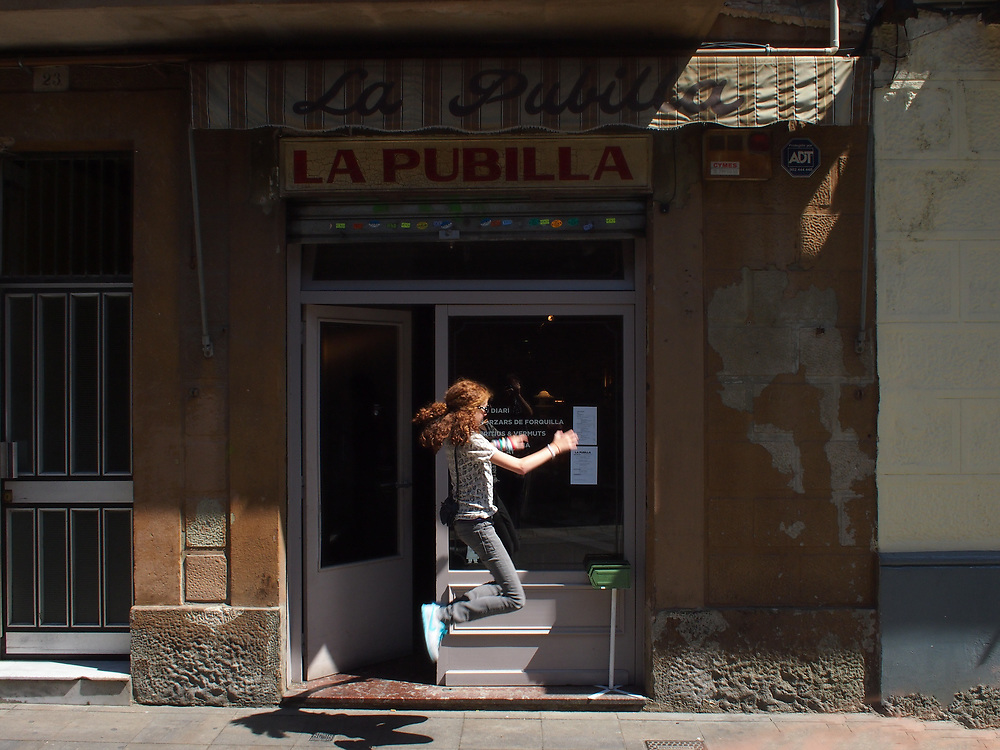 A girl jumps in front of La Pubilla, a restaurant in Barcelona across from La Pubilla market, 2012.