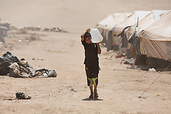 © Licensed to London News Pictures. 27/07/2014. Erbil, Iraq. A young Iraqi refugee carries a container of water at a camp for internally displaced persons (IDP's) at the Kalak Checkpoint near Erbil in Iraqi-Kurdistan. © Licensed to London News Pictures.