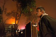 Tenant Richard Fowlkes looks on as the San Jose Fire Department works to put out a double house fire near Margaret St. and South 2nd St. in San Jose, California, on May 10, 2015. (Stan Olszewski/SOSKIphoto)