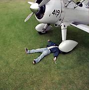 young man lying on ground near wheel of biplane
