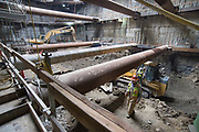 Inside the station headhouse, workers change out the shift for the bulldozer operator hauling material to be excavated.