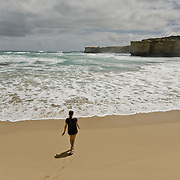 Girl walking on the beach along the Great Ocean Road.