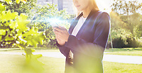 Portrait of young attractive businesswoman using smartphone in park