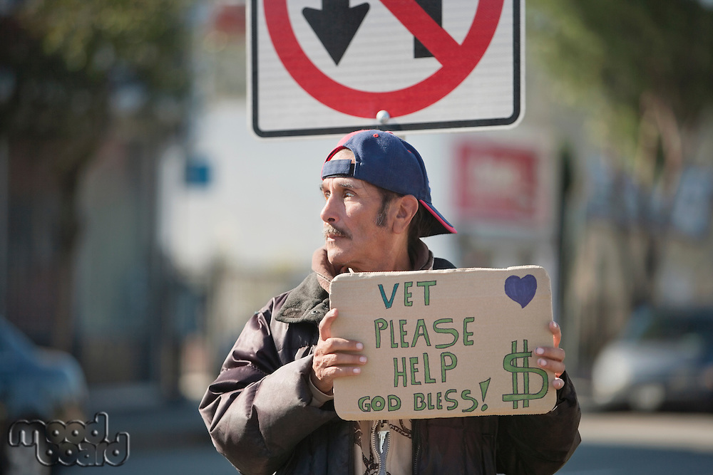 Homeless person with placard in front of road sign