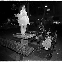 Mom, baby and sister rest after the big parade on the streets of Greenwich Village, during Halloween, in NYC.
