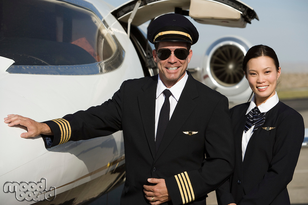 Portrait of mid-adult airline pilot and flight attendant in front of  airplane.