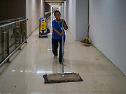 "24 DECEMBER 2015 - BANGKOK, THAILAND:  A worker cleans the floors in a not yet finished hallway in the new domestic terminal at Don Muang (also spelled Don Mueang) International Airport. The new terminal had its ""soft"" opening Dec. 24. Don Muang is the airport used by low cost airlines serving Bangkok and is now the largest airport in the world for low cost carriers. In 2014, more than 21million passengers used Don Muang. Don Muang International Airport is the oldest airport in Asia and one of the oldest airports in the world. It started functioning as an airfield in 1914.    PHOTO BY JACK KURTZ"