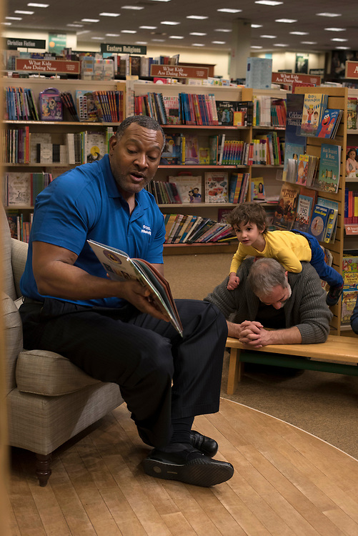 Nelson Batista pauses while crawling on his father Aaron Batista to listen to Dr. Anthony Hamlet - superintendent of Pittsburgh Public Schools - read to students from Colfax Elementary School at the Barnes & Noble at The Waterfront.