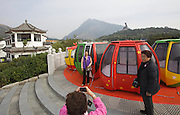 Lantau island. Tian Tan Buddha seen from Ngong Ping Skyrail. Tourists taking souvenir photos with old cable cars.
