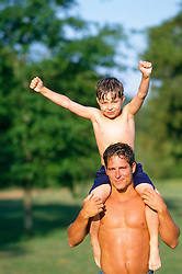 Boy cheering while sitting on the shoulders of a shirtless man