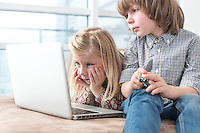 Brother and sister looking at laptop in living room