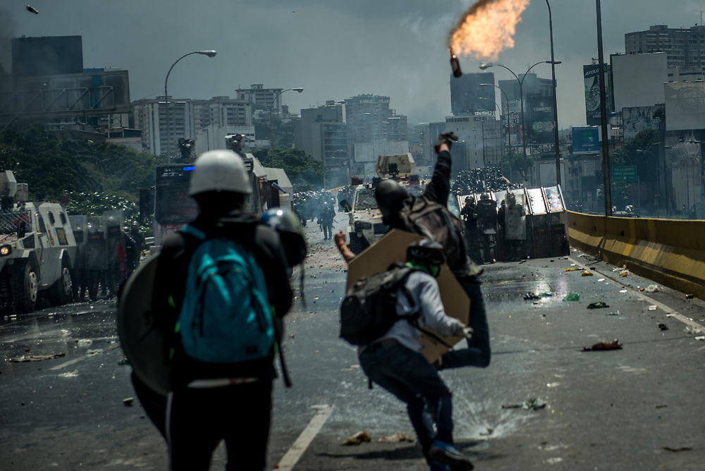 CARACAS, VENEZUELA - MAY 10, 2017:  Anti-government protesters hurl stones and molotov cocktails during clashes for control of the Francisco Fajardo highway with members of the National Police, who responded with a water cannon, and by heavily tear gassing and firing rubber bullets and buckshot at them.  The streets of Caracas and other cities across Venezuela have been filled with tens of thousands of demonstrators for nearly 100 days of massive protests, held since April 1st. Protesters are enraged at the government for becoming an increasingly repressive, authoritarian regime that has delayed elections, used armed government loyalist to threaten dissidents, called for the Constitution to be re-written to favor them, jailed and tortured protesters and members of the political opposition, and whose corruption and failed economic policy has caused the current economic crisis that has led to widespread food and medicine shortages across the country.  Independent local media report nearly 100 people have been killed during protests and protest-related riots and looting.  The government currently only officially reports 75 deaths.  Over 2,000 people have been injured, and over 3,000 protesters have been detained by authorities.  PHOTO: Meridith Kohut