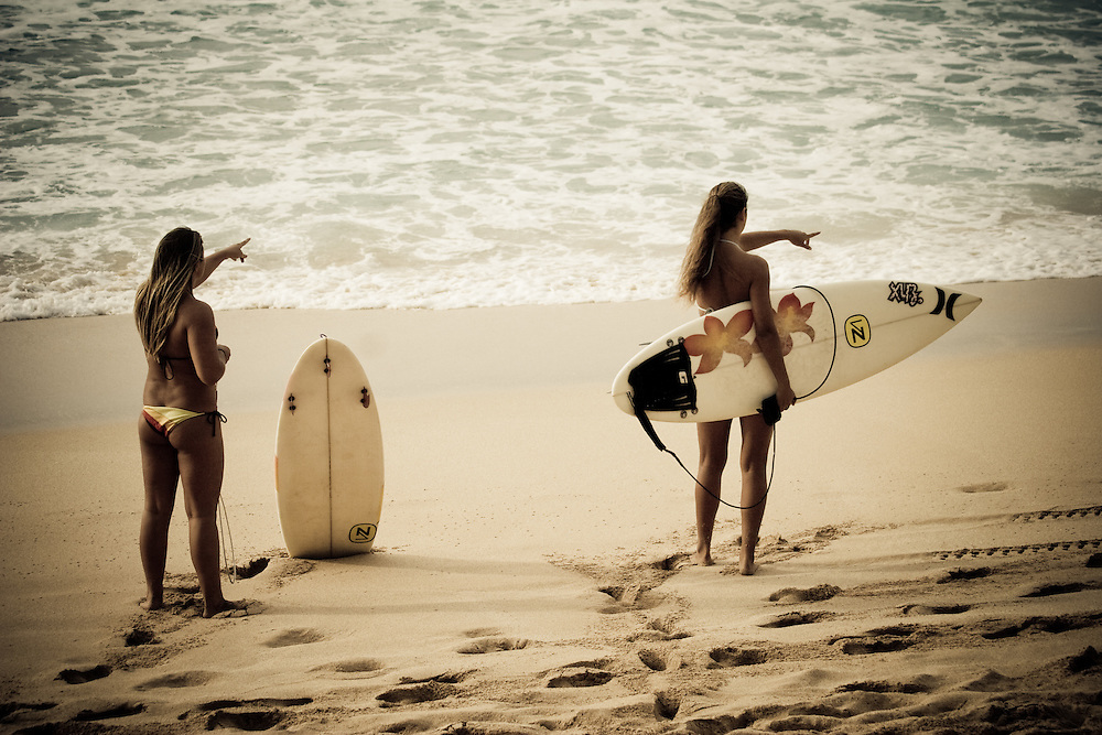 Two female surfers point out to Banzai Pipeline from the beach on the north shore of Oahu, Hawaii, USA.