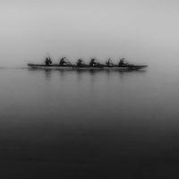 Men rowing a boat in the fog.