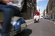 Two men riding motor scooters on the street.