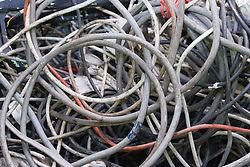 A pile of armoured copper cable waiting to be stripped at a metal recycling centre,