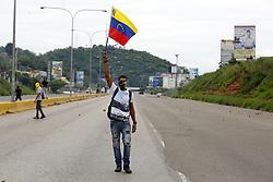 May 3, 2017 - Valencia, Carabobo, Venezuela - Un joven camina con una bandera de Venezuela, luego que la marcha donde participaba fuera reprimida con gas lagrimogeno por la Guardia Nacional, en el sector San Blas de Valencia, estado Carabobo. Foto: Juan Carlos Hernandez (Credit Image: © Juan Carlos Hernandez via ZUMA Wire)