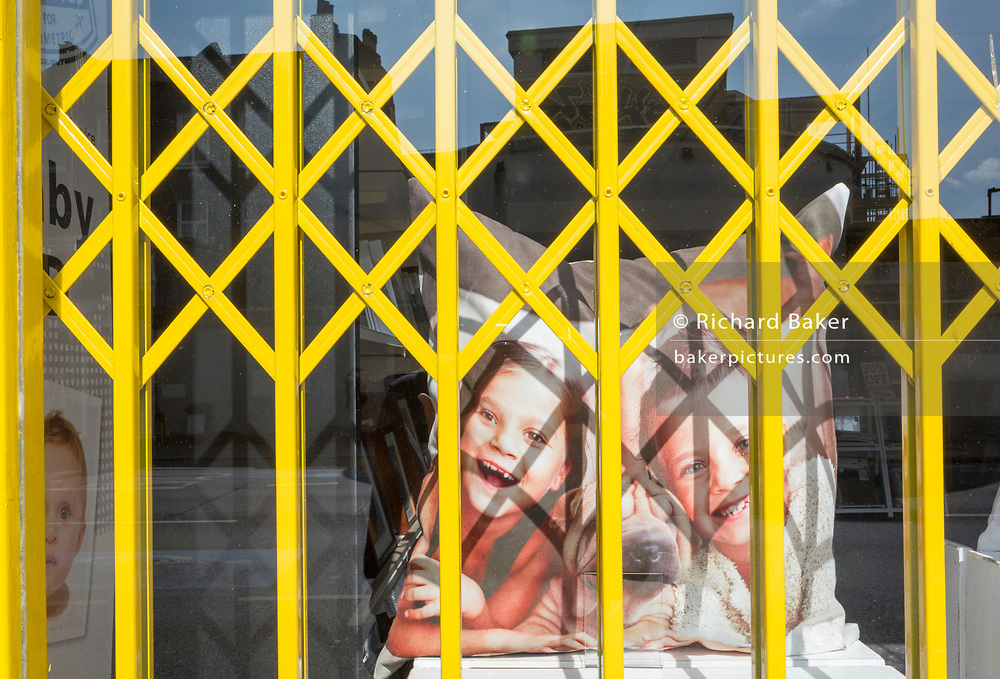 As the second week of the Coronavirus lockdown continues around the capital, and the UK death toll rising by 563 to 2,325, with 800,000 reported cases of Covid-19 worldwide, two young girls smile with their pet dog on a printed cushion in the window of a Snappy Snaps shop in Clapham - a metaphor for family isolation and social distancing during the pandemic, on 1st April 2020, in London, England.