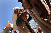 Afghan refugees loading bags of US Aid wheat in Peshawar, Pakistan. 2002