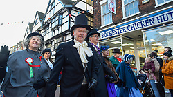 © Licensed to London News Pictures. 08/12/2019. ROCHESTER, UK.  Participants walk through a 'snow' storm during the annual Dickensian Christmas Festival in Rochester.  The Kent town is given a Victorian makeover to celebrate the life of the writer Charles Dickens (who spent much of his life there), with Victorian themed street entertainment, costumed parades and a Christmas market.  Photo credit: Stephen Chung/LNP
