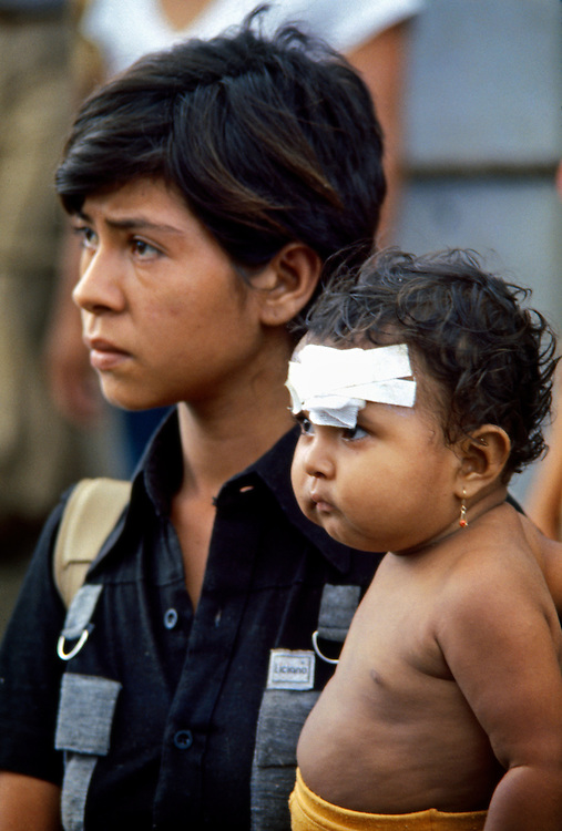 Young Nicaraguan refugees watch as government National Guard troops enter Masaya, Nicaragua looking for suspected Sandinista rebels and supporters.