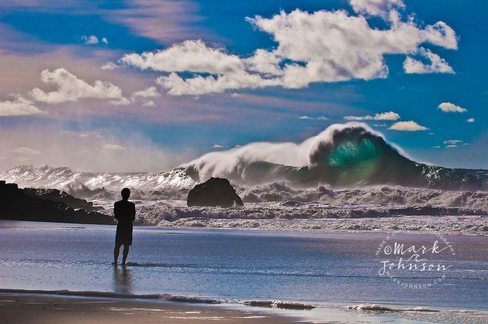Man watching large winter storm surf breaking off the Na Pali coast, Kauai, Hawaii