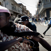 Demostrators run during clashes in central Dakar, Senegal Friday, Feb. 17, 2012.<br /> Anti-government protesters and police clashed for a third consecutive day Friday, engaging in running street battles of rock throwing and tear gas in the streets of Dakar's downtown Plateau neighborhood. Demonstrators are defying a government ban on protests to call for the departure of 85-year-old President Abdoulaye Wade, who is running for a third term in next week's election.