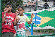 Two young boys hang on the chain link fence surrounding a small concrete football pitch at Santo Amaro favela, Rio de Janeiro, Brazil. According to Patrick Ashcroft an English (Stockport) researcher and teacher who lives in the favela, it is fairly quiet and non violent. There is a heavily armed police presence in the favela.<br /> Picture by Andrew Tobin/Focus Images Ltd +44 7710 761829<br /> 20/06/2014