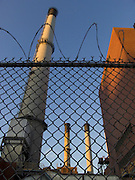 upward view of smoke stacks behind razor wire fence