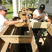 Volunteer Berry Snyder and Ronnie Schutkesting, Facilities Director at the Private John Allen Fish Hatchery, hammer in a support beam ias they prep for a new composite decking to be installed on the front porch of the Fish Hatchery home in Tupelo on Wednesday morning.