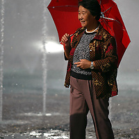 An old Chinese woman is holding an umbrella in the down town of Hoh-hoh city, were they are celebrating the 60th anniversary of founding the Inner Mongolia autonomous region. China. Aug-22-2006. Photo: Stringer