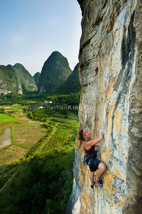A woman rock climber scales a cliff known as The Egg near Yangshuo, China (Model Released, Kre Reischel).