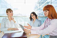 Businesswomen discussing over table PC at table in office