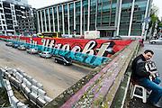 Een straatmuzikant speelt op zijn accordeon bij de bouwput waar weer water in de Catherijnesingel gaat stromen. In de achtergrond staat de graffitie met 'Welkom in Utrecht'.<br /> <br /> A busker is playing his accordion near the construction area where Utrecht is changing a road into a canal again. The graffiti on the wall says 'Welcome in Utrecht'.