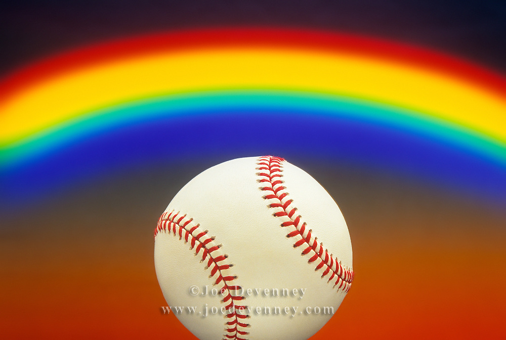 Still life of a baseball with a rainbow background