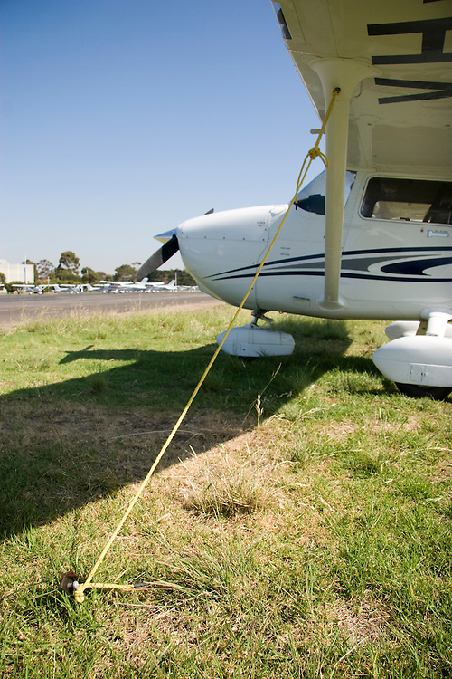 Detail of a tie-down rope on a Cessna 172, pegged to grass