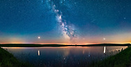 A 160&deg; panorama taken July 5/6 of the summer Milky Way and the array of summer 2018 planets over the prairie pond near home in southern Alberta. <br /> <br /> Mars is bright to the left, Saturn is dimmer and at centre in the Milky Way, while bright Jupiter is at right. Mars and Jupiter nicely flank the Milky Way, and cast glitter paths on the water. The arcing line joining the planets defines the arc of the ecliptic, always low in the south in northern hemisphere summer. Mars was approaching Earth and brightening at this time heading for a late July opposition.<br /> <br /> The sky is deep blue with solstice twilight. Several satellite trails punctuate the sky. <br /> <br /> This is a panorama with 2 tiers of 6 segments each, stitched with Adobe Camera Raw. Each segment was 20 seconds at f/2 with the 20mm Sigma Art lens and Nikon D750 at ISO 6400.<br /> <br /> Glow effect and vignetting added with Zone System Express extension effects.