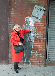 Woman being playful with an outdoor poster of Albert Einstein
