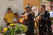 A family at the gravesite of a loved one with a mariachi band at the San Miguel cemetery during the Day of the Dead Festival known in spanish as Día de Muertos on November 2, 2013 in Oaxaca, Mexico.