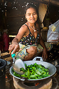 "01 MARCH 2014 - MAE SOT, TAK, THAILAND: A Burmese woman stir fries vegetables for her family in her home in a Burmese community in the forest a few kilometers north of Mae Sot. Mae Sot, on the Thai-Myanmer (Burma) border, has a very large population of Burmese migrants. Some are refugees who left Myanmar to escape civil unrest and political persecution, others are ""economic refugees"" who came to Thailand looking for work and better opportunities.    PHOTO BY JACK KURTZ"