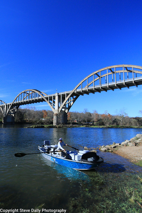 Drift boat with a fly fishing guide on the oars. Cotter Arkansas,