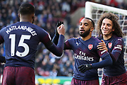 Arsenal forward Alexandre Lacazette (9) celebrates with Arsenal midfielder Matteo Guendouzi (29) and Arsenal midfielder Ainsley Maitland-Niles (15) after scoring his team's second goal during the Premier League match between Huddersfield Town and Arsenal at the John Smiths Stadium, Huddersfield, England on 9 February 2019.