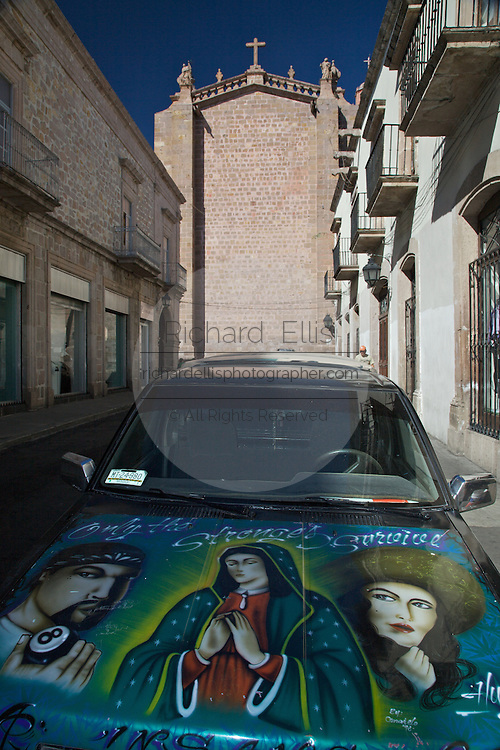 A car painted in religious themes parked behind Morelia Cathedral on the Plaza de Armas Morelia, Michoacan state Mexico. The city is a UNESCO World Heritage Site and hosts on of the best preserved collection of Spanish Colonial architecture in the world. Commissioned by the Duke of Albuquerque, appointed Viceroy to the territories of Mexico, ordered its construction in 1660 which was carried out by the Italian master Vicente Barroso until his death in 1692 it took an additional 52 years to complete. The Cathedral has the highest and bulkiest church towers of the continent.