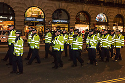 © Licensed to London News Pictures. 20/01/2017. London, UK. After protesting outside the U.S. Embassy in Grosvenor Square against the inauguration of Donald Trump as U.S. President, which took place in Washington DC today, demonstrators stage an impromptu march through the West End, closely followed by the police. Photo credit : Stephen Chung/LNP