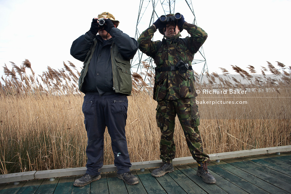 Camouflaged birdspotters peer through binoculars for wildlife at the RSPB's bird and wildlife reserve at Rainham Marshes, Essex