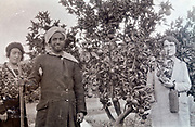 Moroccan farmer posing in fruit trees orchid with two Western women 1930s