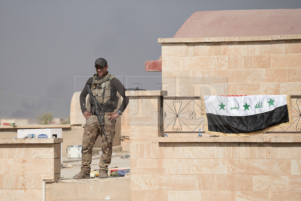 Licensed to London News Pictures. 23/10/2016. An Iraqi Army Counter Terrorism soldier is seen standing guard on the roof of the Mart Shmony Church in Bartella, Iraq.<br /> <br /> Bartella, a mainly Christian town with a population of around 30,000 people before being taken by the Islamic State in August 2014, was captured two days ago by the Iraqi Army's Counter Terrorism force as part of the ongoing offensive to retake Mosul. Although ISIS militants were pushed back a large amount of improvised explosive devices are still being found in the town's buildings. Photo credit: Matt Cetti-Roberts/LNP