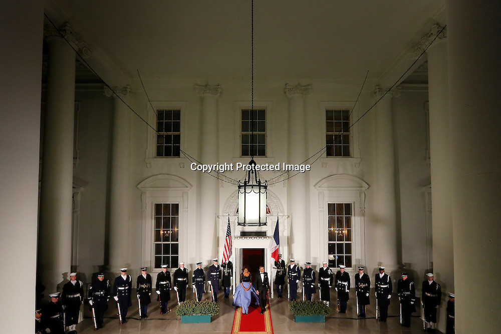 U.S. President Barack Obama and his wife Michelle walk out to greet French President Francois Hollande as he arrives for a State Dinner in his honor at the White House in Washington, February 11, 2014.