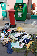 A pile of clothes, books and miscellaneous items left outside a south London charity shop lie useless in the gutter.
